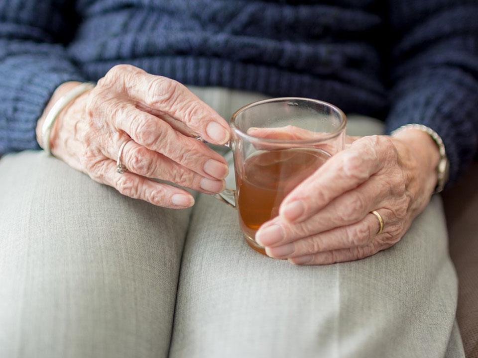 Ältere Person, die Teetasse hält